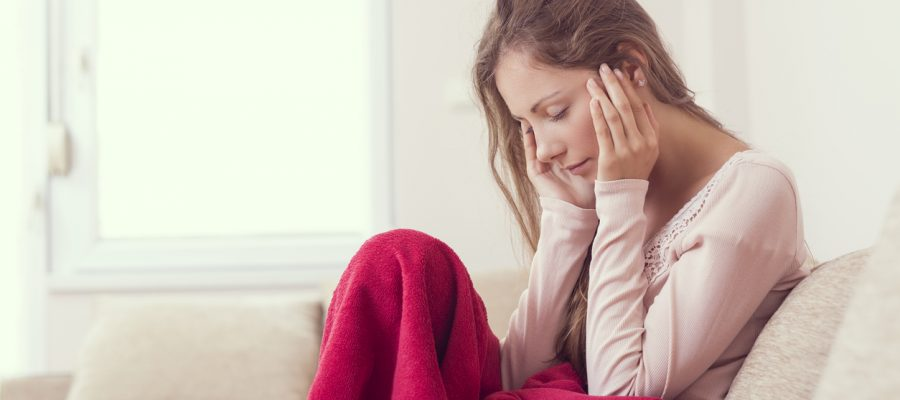 Young woman sitting on a couch, holding her head, having a strong headache. Lens flare effect on the window
